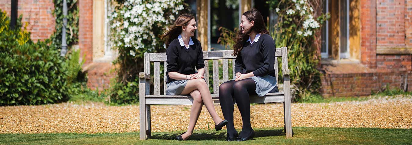 two school girls talking to eachother on a bench