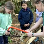 Schoolchildren trying out hack sawing by chopping off small blocks of wood