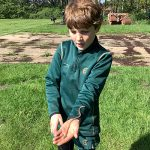 A child holding a long worm in their hand