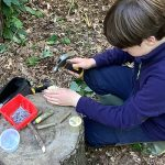 A child working on a project using a hammer, nails and random branches