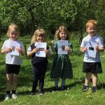 6 young schoolchildren hold up pictures of the bugs they found in the grass