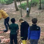 Children looking to balance on a long piece of role tied between 2 trees