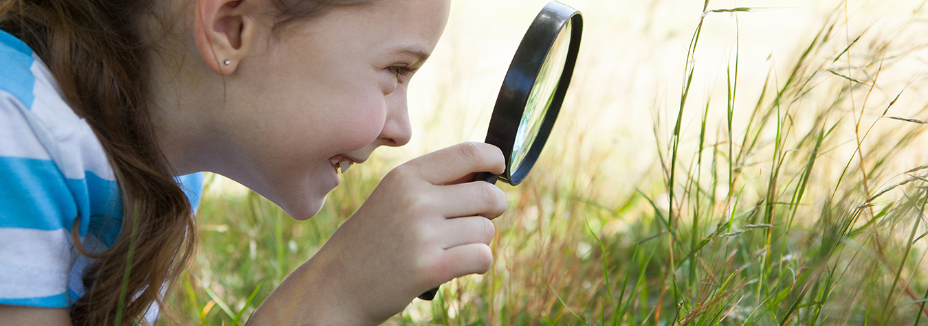 A young girl with a magnifying glass looking at the grass